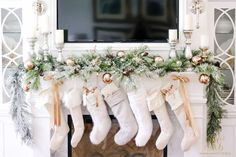 Elegant fireplace mantel decorated for Christmas with flocked evergreens and stockings. white, neutral, beautiful