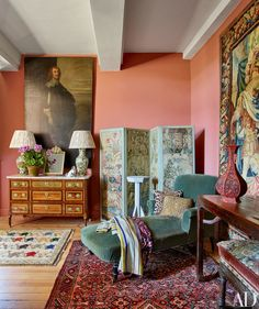 An 18th-century screen stands next to a velvet-clad 1920s chaise longue in a corner of the master bedroom.  Wall colour: F & B Red Earth?
