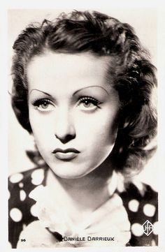 """""""French actress and singer Danielle Darrieux (1917) is an enduringly beautiful, international leading lady. From her film début in 1931 on she progressed from playing pouting teens to worldly sophisticates. In the early 1950s she starred in three classic films by Max Ophüls, and she played the mother of Catherine Deneuve in five films."""" Photo c. late 1930s?"""