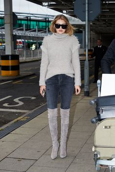 Arriving at London's Heathrow Airport in a gray turtleneck, jeans and suede over-the-knee boots.    - HarpersBAZAAR.com