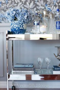 Blue and gray floral wallpaper lines walls accented by gorgeous white wainscoting positioned behind a stunning styled silver Roland bar cart from Worlds Away accented with a blue Chinese vase and stacked books.