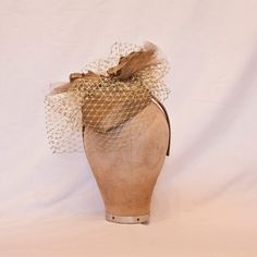 Handmade gold heart shaped hat decorated with gold veiling, flowers and leaves