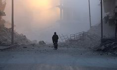 A man cycles near damaged buildings after a strike on the. rebel-held al-Shaar area of Aleppo./NOV16