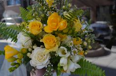 Today's wedding bouquet of yellow and white flowers - freesia, roses, spray roses, fever few, ferns and berries.