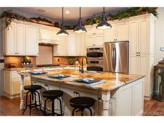 White kitchen with glazed cabinets - large island with counter seating - stainless appliances - Naples, FL