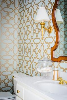 Blue and gold powder room features walls clad in blue and gold trellis wallpaper, Schumacher Cordoba Gold Wallpaper, lined with a lacquered mirror lit by a gold walls conce placed over a white vanity cabinet adorned with gold knobs.
