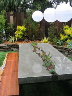 perfect backyard retreat! concrete table, wood bench, lanterns & landscaping!