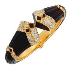 """BOUCHERON . Stunning bangle created by Boucheron, Paris in the 1980's. Features carved ebony wood on yellow gold accented with diamonds and rubies. Fits up to 6.5"""" wrist.  The bangle is graduating from 7/8"""" at the opening to 3/8"""" on the back.Has French gold hallmarks, Boucheron maker's mark and a serial number. (=)"""