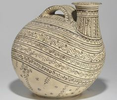 A DAUNIAN POTTERY ASKOS  APULIA, CIRCA 3RD CENTURY B.C.  The globular body with a cylindrical neck, a flaring mouth, and a wide strap handle, richly decorated in parallel bands with scrolling, wave, vines and other decorative elements 14¼ in. (36.2 cm.) high