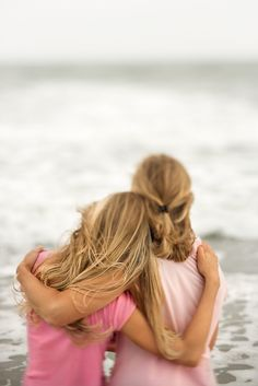 Rear view of a mother and daughter embracing at the beach. Vertical shot.