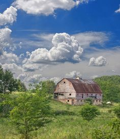 More farmer's wife - blue, green, grey of barn, rust, brown, some remaining red pain, grey sky, blue sky, white clouds, golden grass