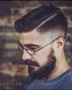 Man with tailored hairstyle with tapered sides, thick beard, mustache, and circular glasses.