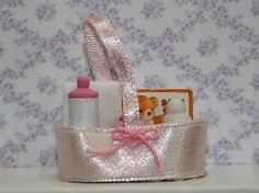 Baby Needs in Pink (TA221) - Nursery. Over 10,000 similar dolls house miniature products available from www.thedollshousestore.co.uk