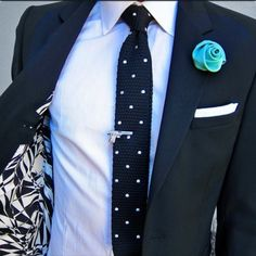 A very rad look, right down to the flower lapel and gun tie clip.