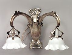 Pair of French Art Nouveau brass 2 arm wall sconces with fleur de lis front panel and white scalloped glass shades