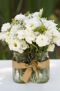 Mason jars are filled with white lisianthus and ranunculus flowers for a rustic fee