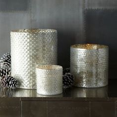 contemporary candles and candle holders by West Elm (the first thing i thought of is saving my cans and using decorative spray paint.  home depot and lowes both sell one called hammered metal that have a similar texture.  i'd also spray the inside gold and just place a votive inside)