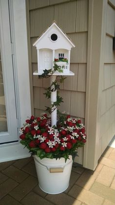 She sticks a table leg from Lowe's into a bucket. The reason? This front porch idea is gorgeous!