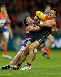 Dylan Shiel of the Giants is tackled by Liam Picken of the Bulldogs during the 2016 AFL First Preliminary Final match between the GWS Giants and the Western Bulldogs at Spotless Stadium on September 24, 2016 in Sydney, Australia.