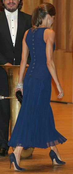 Doña Letizia wore a Felipe Varela midi peacock blue dress, with a silhouette, fashioned with a fitted sleeveless bodice, round neck, drop-waist and a flared pleated skirt reminiscent of a ballroom gown,  black Tod's rhinestone toggle clutch,Yanes blue topaz chandelier earrings, joyas de pasar diamond bracelets, green stone ring, and navy Nina Ricci suede pumps. Queen Letizia attends Princess of Asturias Awards concert. 19 Oct 2017