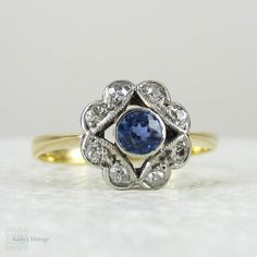 (http://www.addysvintage.co.uk/antique-sapphire-diamond-engagement-ring-art-nouveau-cornflower-blue-sapphire-and-diamond-cluster-daisy-ring-with-pierced-design-18-carat/)