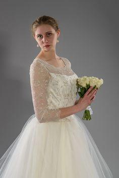 Svatební šaty s tylovou sukní Jemně smetanové svatební šaty s krajkovým živůtkem a tylovou sukní. Živůtek je z vyšívaného tylu kovovou nití, vzadu na skrytý zip a knoflíčky. Dlouhý krajkový rukáv, zakončený obloučky. Sukně je kolová, z několika vrstev tylu - celková spotřeba tylu byla 28m. Není potřeba spodnička, sukně je sama o sobě hodně široká. Velikost ...