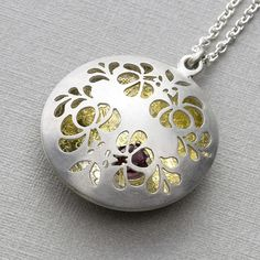 "Pendant | Simone Walsh.  ""Floral open locket"".  Sterling silver, 23k silver gilt and rhodolite gem"