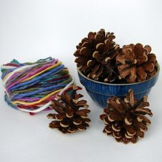 Pinecone weaving is a wonderful first handwork experience for children as young as two years old. The youngest children can simply wrap their pinecones with appealing colors while older family members can focus on creating studies in color, pattern and texture. The finished pieces look lovely displayed in a bowl, on the nature table, or even on the Christmas tree. They also make a beautiful and natural gift from the heart, made with love by small hands.