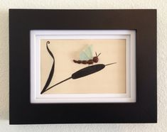 Genuine sea glass and pebbles collected from a beach on the central coast of California arranged in a collage of a dragonfly on a cattail.