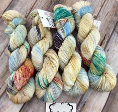 Golden Feather is a speckle-dyed yarn with a warm gold base color and shots of bright baby blue, deep gray, and speckles of peach and teal throughout. Every skein is unique and this colorway may pool due to how the colors are placed during the dye process. Skeins can vary quite a bit