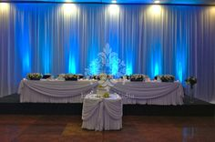 Backdrop with blue uplights, bridal and cake table skirting with scalloping