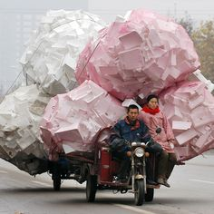A man and a woman ride a motor tricycle carrying bags of recyclable polystyrene in Shouguang