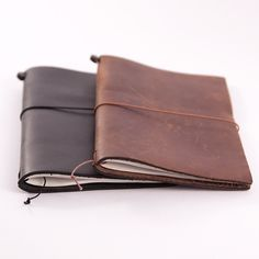 MIDORI TRAVELER'S NOTEBOOK / Midori - The Midori Traveler's Notebook consists of a removable paper notebook, wrapped in a thick flap of leather, held by an elastic band. Each leather cover is made by hand in Chiangmai, a city in northern Thailand. If you love the feel of pen on paper, the smell of leather and have stories to tell, you will want this notebook in your bag or pocket.