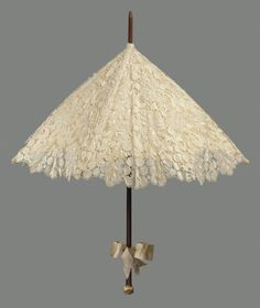 Cream colored silk bobbin lace parasol in heavy symetrical design of ornamental leaves, lined with cream colored satin bow tied on plain brown wooden handle, knob of carved ivory with monkey picking fruit at end of handle. Clear Umbrella, Lace Umbrella, Lace Parasol, Vintage Umbrella, Under My Umbrella, Lace Dress, Vintage Outfits, Vintage Fashion, Umbrellas Parasols