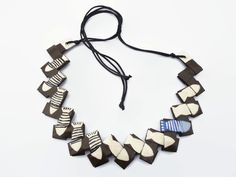This abstract necklace is handcrafted from a recycle shopping bag and I decorated it with acrylics with small white fishes black striped. I added one fish in two shades of light blue. It's a fun and playful necklace, for original  women with a nice sense of humor. The length is adjustable, you can adapt it to your liking. Its black cord is super soft and easy to wear against the neck. It's a first quality cord whose characteristics are the smoothness and brightness of the colors.