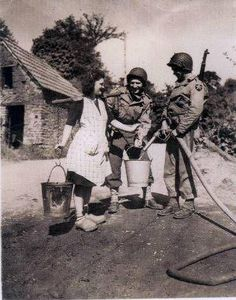 Marie-Jeanne Brossard, a farmer's daughter wearing clogs, poses while a GI is filling her buckets with filtered water. The other GI is Bernard Dargols. Normandy Ww2, D Day Normandy, World War One, Second World, Military Photos, Military History, War Dogs, Women In History, Us Army