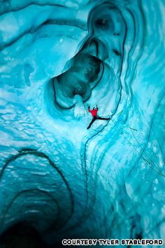 Mark Jenkins climbs an overhanging wall into a dark ice chimney inside the Langjokull Glacier,. The black striations are layers of volcanic ash deposited over centuries of eruptions.