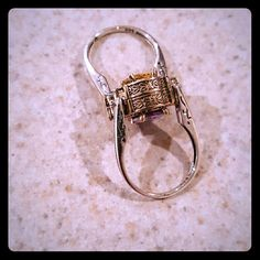 NWOT Sterling Silver Two Way Ring NWOT Sterling Silver Two Way Ring! One side has a Lavender Stone with lots of CZ's all around it, On the other side a Yellow Stone with lots of CZ's as well! Both set in an antique Gold Tone Setting, each with a Sterling Silver band. (Stamped 925)  Very Unique and definitely not one you'll see often. Jewelry Rings