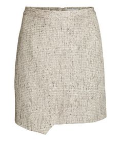 Short woven skirt with a sewn-in wraparound, and a visible zip at the back. Lined.