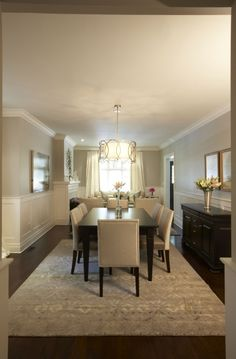 Elegant, sophisticated dining room design with soft gray walls paint color, espresso stained dining table, ivory leather dining chairs with nailhead trim, blue & gray rug, espresso stained buffet, wainscoting and brass Sausalito Five Light Chandelier.