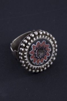 Silver ring, first half of 1900. Marocco The silver ring has a central polychrome glass bead, called stone of Goulimine. These glass beads, originally made in Venice, look like eyes and are therefore considered to be protective. Bibliography: A. von Cutsem, Anelli Etnici, Milano 2000, p.25   Origin: Morocco Age: First half 1900 Materials: Silver, glass beads.