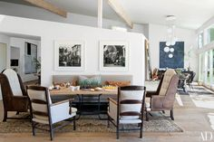 In Patrick Dempsey's Malibu, California, home, fashion photographs by Melvin Sokolsky are displayed in a dining area outfitted with chairs from Lucca Antiques and a custom-made Teak Nichols Design table; the home was decorated by Estee Stanley Interior Design.