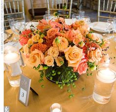 The couple chose shorter centerpieces, so the flowers wouldn't block the view. Coral colored roses, gerberas and hypericum berries filled glass cylinder vases and were arranged around small tea-light candles.