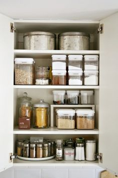 lazy susan, clear stacking containers and glass apothecary jars used to organize pantry