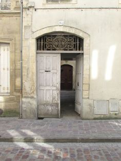 A doorway in Bayeux. I love the sunlight on the wall and street. Photo by Shu