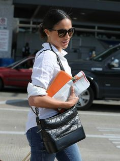 Meghan Markle.. J Crew Perfect shirt, Zara jeans, Madewell Panama hat, Chanel Gabrielle bag, J Crew Franny shades, Stow First Class Tech case, and Birks earrings and ring..