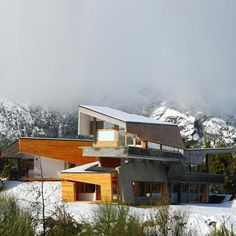 Ribbon House. This mountainside house by G2 Estudio in Argentine Patagonia is wrapped in a stone and wood facade.