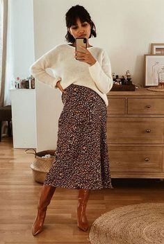 6 Reasons To Love The Midi Skirt And Boots Combo: Fashion Blogger Sherlock Diary wearing a white oversized sweater, a leopard skirt and brown tall boots. Fall outfit, spring outfit, street style, casual outfit, casual style, blogger style, fashion 2019, fashion trends 2019, midi skirt outfit, #fashion2019 #streetstyle #casualstyle #fallstyle #springstyle #ootd #trendingrn