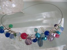 FARBRAUSCH  eine irisierende, olivenförmige Perle aus Kyanit in taubenblau, kleine grüne Grossular-Kugeln (Granat), facettiert, facettierte Linsen in pink und lavendelfarbene, facettierte Kugeln aus Alexandrit, Apatit-Perlen in meerblau, facettierte Würfel aus hell-lila Amethyst, zartgrüne und facettierte Kugeln aus Prehnit,   tintenblaue und smaragdgrüne Jadekugeln (gefärbt), Zuchtperlen in türkis,   Tropfen aus klarem, hellem Aquamarin und   Kugeln aus Opalit
