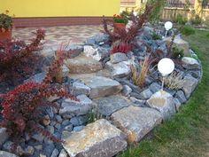 Řešení svahu pod domem pomocí lomových kamenů, prokládaných menšími kameny a prosypávaných drobným štěrkem stejné barvy.